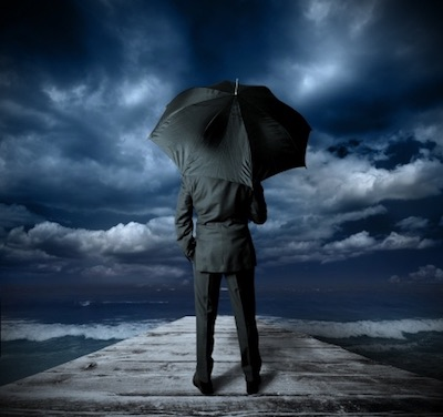 Businessman with umbrella on a pier watching storm gather