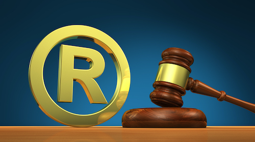 Registered trademark law business concept with golden trade mark symbol and a wooden gavel 3D illustration.